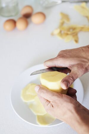 closeup of a caucasian man in the kitchen cutting some potatoes, to prepare a typical tortilla de patatas, a spanish omelet Stok Fotoğraf