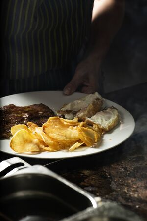 closeup of a woman in a professional kitchen preparing a combo platter consisting of some fried eggs, some potato chips and some slices of sirloin Stok Fotoğraf