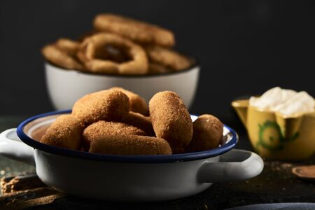 some spanish croquettes in a white and blue enamel plate on a table and some calamares a la romana, fried battered squid rings typical of spain, in the background, next to a mortar with aioli sauce