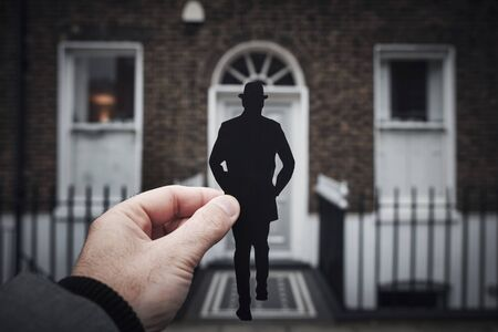 closeup of the hand of a man holding a paper cutout in the shape of a man, wearing a bowler hat, walking to the front door of a typical victorian house, in London, United Kingdom Stok Fotoğraf