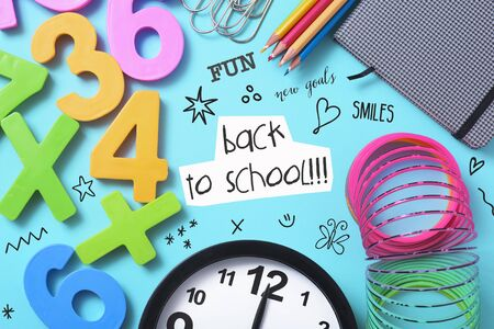 a clock, some pencil crayon of different colors, a notepad, some paper clips, some numbers of different colors, some drawings and the text back to school on a bright blue background