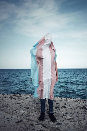 a young person covered with a transgender pride flag, with the ocean in the background