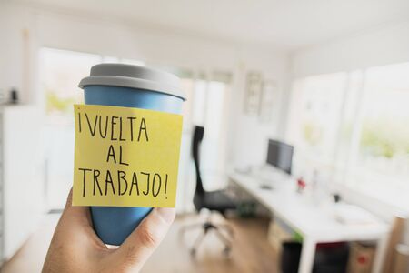 closeup of a man having a cup of coffee in his hand, with a sticky note with the text vuelta al trabajo, back to work written in spanish, in front of his office desk