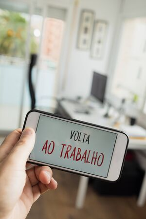closeup of a man sitting at his office desk, and a smartphone in the foreground with the text volta ao trabalho, back to work written in portuguese, in its screen