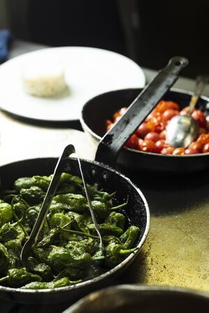 closeup of some cooked green peppers and cherry tomatoes in different frying pans, in a professional kitchen Stok Fotoğraf