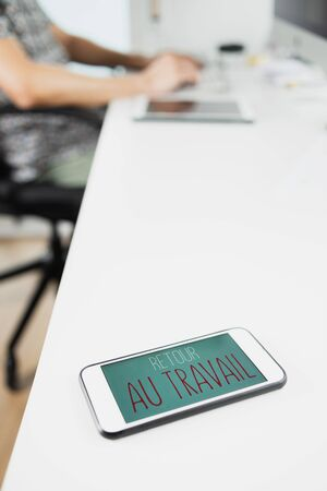 closeup of a man sitting at his office desk, and a smartphone in the foreground with the text retour au travail, back to work written in french, in its screen Stok Fotoğraf