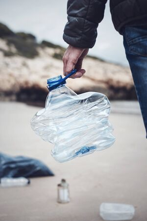closeup of a caucasian man collecting garbage on a lonely beach, as an action to clean the natural environment Standard-Bild