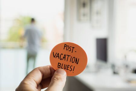 closeup of a man at the office with a note in his hand, with the text post-vacation blues written in it, and a man seen behind standing in the background Фото со стока
