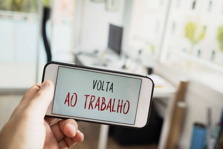 closeup of a man at the office with a smartphone in his hand with the text volta ao trabalho, back to work written in portuguese, in its screen