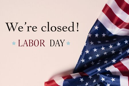 enkele vlaggen van de Verenigde Staten en de tekst we zijn gesloten, dag van de arbeid, op een beige achtergrond