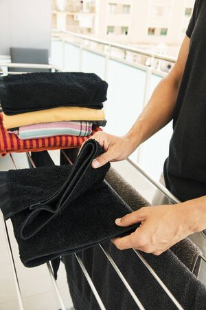 closeup of a young caucasian man folding clothes after unhang them from a drying rack in a balcony