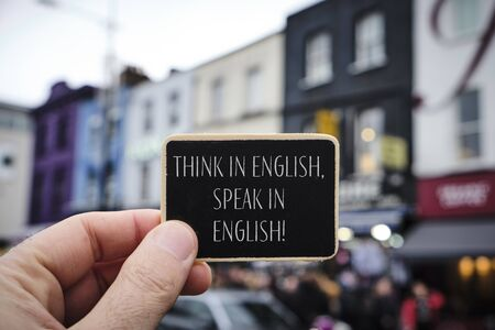 closeup of the hand of a caucasian man holding a black signboard with the text think in English speak English written in it, on the street, in the popular Camden Town in London, United Kingdom