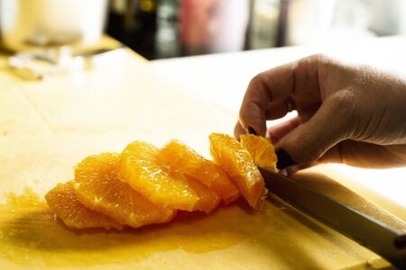closeup of a woman cutting an orange in slices in a professional kitchen Stock fotó