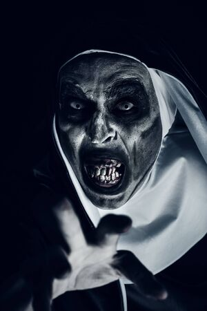 Closeup of a frightening evil nun, with bloody teeth and scary eyes, wearing a typical black and white habit, doing a threatening gesture with her hand Banque d'images