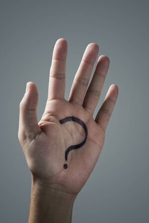 man with a question mark painted in the palm of his hand on an off-white background
