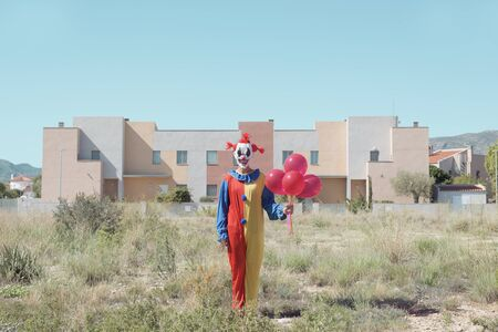 a creepy clown wearing a colorful yellow, red and blue costume outdoors, holding a bunch of red balloons in his hand
