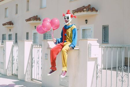 a creepy clown wearing a colorful yellow, red and blue costume, holding a bunch of red balloons in his hand, sitting in front of a row of houses 版權商用圖片