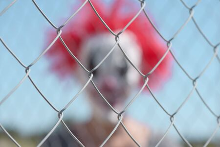 closeup of a chain-link fence in focus, and a blurred scary clown in the background Foto de archivo