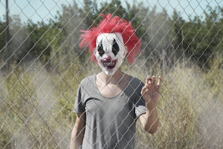 a scary clown looking to the observer with a threatening look through the wires of a fence, in front of an abandoned natural landscape