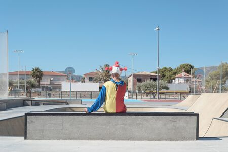 a scary clown, wearing a colorful yellow, red and blue costume, seen from behind, smoking a cigarette, sitting in an outdoor public sports complex Foto de archivo
