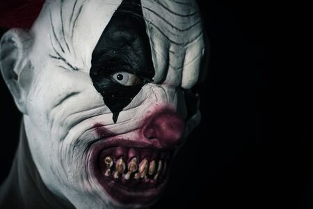 closeup of a scary evil clown with white eyes, bloody teeth and a threatening look staring at the observer, against a black background