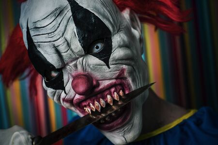 closeup of a scary evil clown, with red hair, white eyes and bloody teeth, with a knife in his mouth staring at the observer with a threatening look