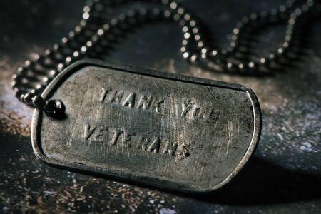 Nahaufnahme einer rostigen Hundemarke mit dem Text danke Veteranen darin geschrieben, auf einer rustikalen grauen Oberfläche