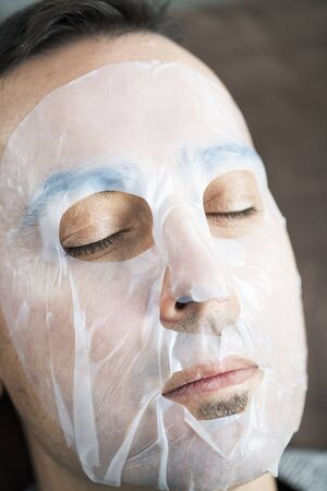 Closeup of a handsome caucasian man wearing a bio-cellulose sheet mask