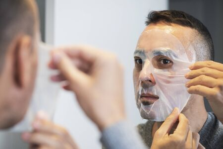 Closeup of a handsome caucasian man applying a bio-cellulose sheet mask to his own face