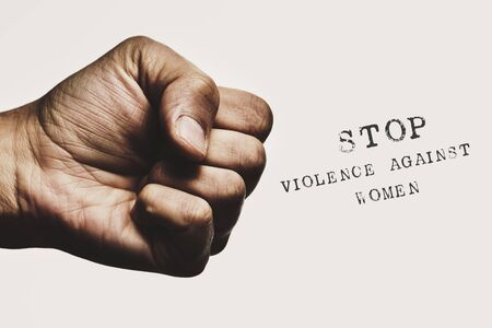 Closeup of a man with his fist threateningly closed and the text stop violence against women against an off-white