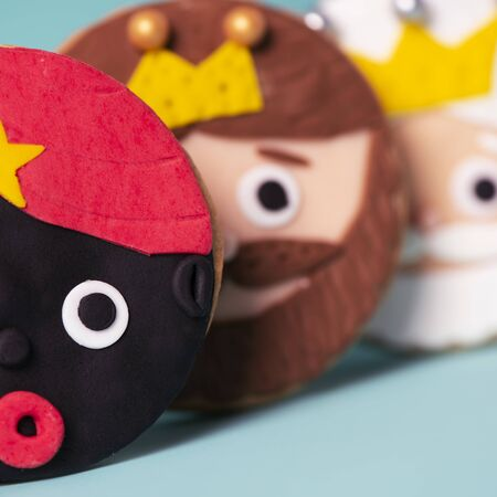 Closeup of some homemade cookies in the shape of the three wise men on a blue Stock Photo