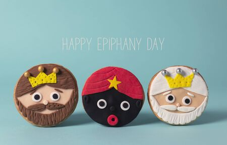 closeup of some homemade cookies in the shape of the three wise men and the text happy epiphany day on a blue background Banque d'images
