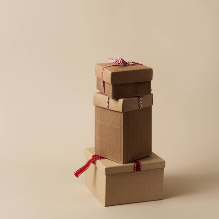 a pile of brown gift boxes tied with different strings and ribbons, on a brown background with some blank space around them