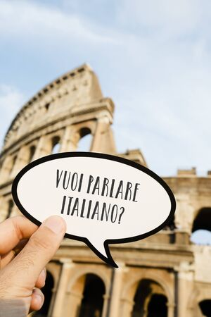 closeup of the hand of a caucasian man holding a sign with the question vuoi parlare italiano? do you want to speak Italian, written in Italian, in front of the Colosseum, in Rome, Italy