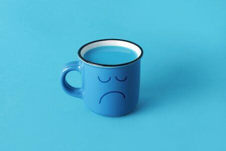 gros plan d'une tasse bleue, avec un visage triste dessiné dedans, et plein d'un liquide bleu, sur fond bleu