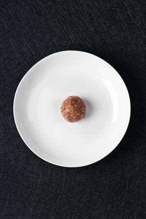 high angle view a raw homemade meatball in the center of a white ceramic plate, on a black stone table or countertop