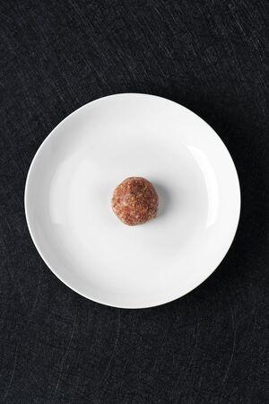 hoge hoek bekijken een rauwe zelfgemaakte gehaktbal in het midden van een witte keramische plaat, op een zwarte stenen tafel of aanrecht