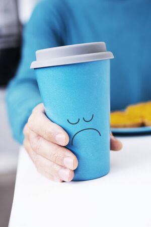 Closeup of a caucasian man, sitting at a white table at breakfast, grabbing a blue cup of coffee with a sad face drawn in it Stockfoto