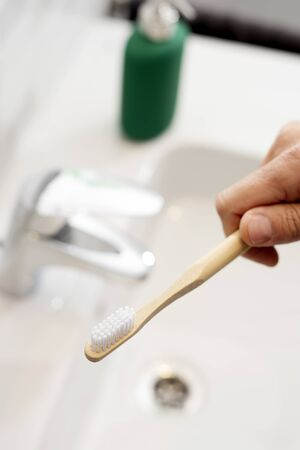 Closeup of a caucasian man using a bamboo toothbrush in the bathroom