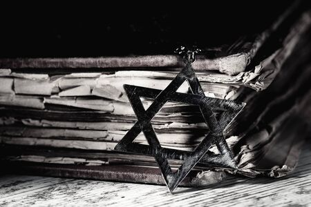 closeup of an old and rusty pendant in the shape of the star of david next to an old book, on a rustic wooden surface, with a dramatic light