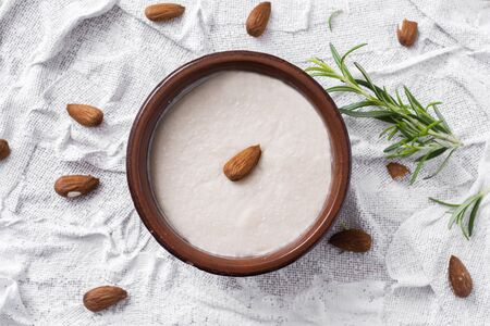 high angle view of an earthenware bowl with menjar blanc, a dessert made with almonds and sugar typical of Catalonia, Spain, on a white textured surface