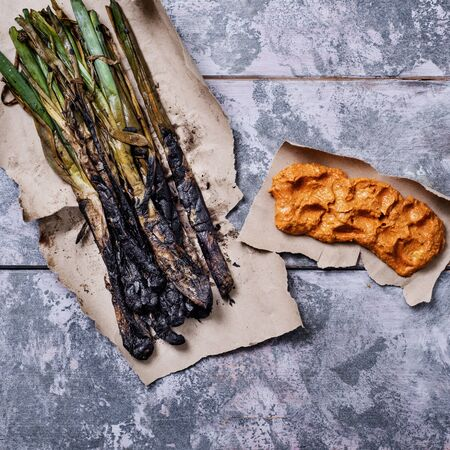 high angle view of some grilled calcots, sweet onions typical of Catalonia, Spain and some romesco sauce to dip them in it, on a gray rustic wooden table