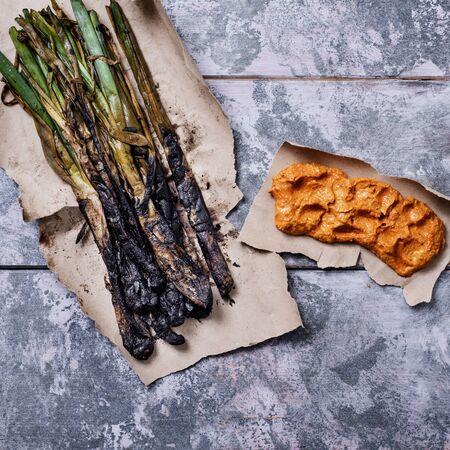 widok z dużego kąta grillowanych kalcotów, słodkiej cebuli typowej dla Katalonii, Hiszpanii i sosu romesco, aby je w nim zanurzyć, na szarym rustykalnym drewnianym stole