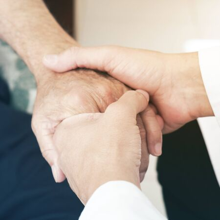 Close up of a caucasian man taking the hand of a senior caucasian patient man