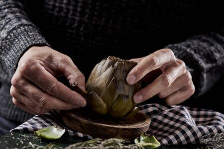 closeup of a man removing the outer leaves of a roasted artichoke in a wooden plate on a table
