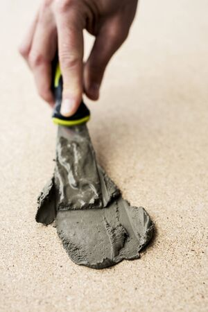 Close up of caucasian man spreading some concrete with a scraper on a fiberboard surface