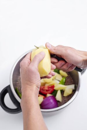 high angle view of a caucasian man chopping a raw potato as he is preparing a lentil stew, in a stainless steel saucepot, placed on a white countertop 版權商用圖片
