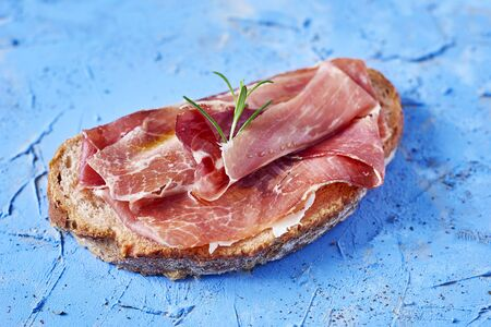 closeup of spanish pa amb tomaquet, a slice of bread with tomato, topped with serrano ham on a blue textured surface Reklamní fotografie