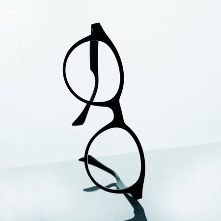 closeup of a pair of black eyeglasses on a reflecting surface against a white background Stok Fotoğraf