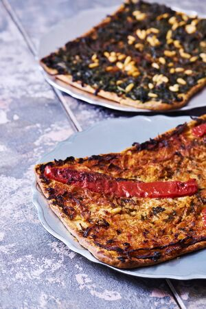 closeup of two slices of different coca de recapte, a typical catalan savory cake similar to pizza, one made with onion and red pepper, and the other one made with spinach, pine nuts and raisins